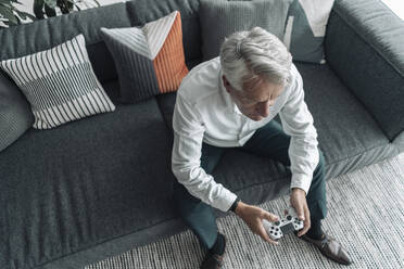 Businessman playing video game while sitting on sofa at office - GUSF04542