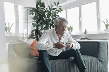 Senior businessman playing video game with concentration while sitting on sofa at office - GUSF04545