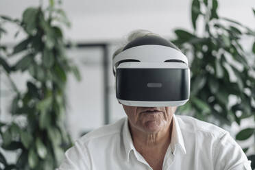 Businessman wearing virtual reality eyeglasses while sitting at office - GUSF04548