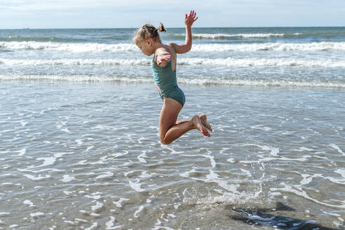 Girl gymnast jumping over sea at beach on sunny day - OGF00597