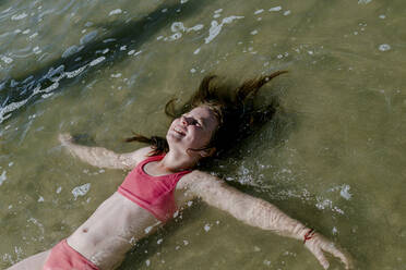Girl lying down in water at beach on sunny day - OGF00600