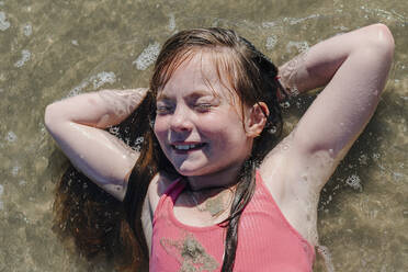 Girl lying on back with hands behind head in water during sunny day - OGF00603