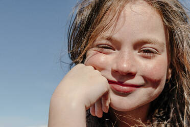 Close-up of girl with hand on chin during sunny day - OGF00606
