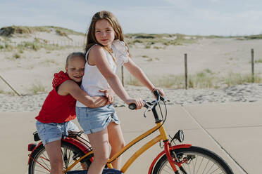 Younger sister embracing girl while sitting on bicycle during sunny day - OGF00609