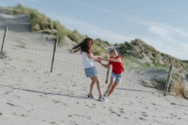 Sisters playing on sand at beach during sunny day - OGF00612