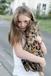Girl carrying domestic cat while standing on street - OGF00621