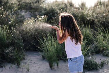 Girl blowing while standing on sand during sunny day - OGF00627