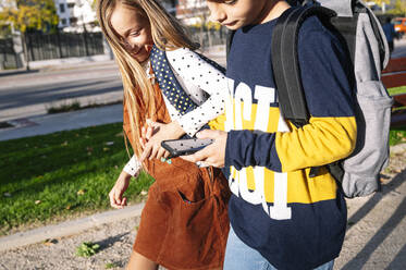 Sibling holding hands while using smart phone walking in public park on sunny day - JCMF01560