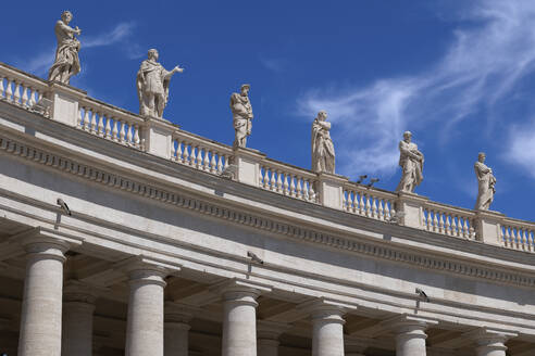 Saint statues on St. Peter's Basilica against blue sky on sunny day, Vatican City, Rome, Italy - ABOF00572