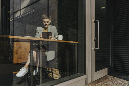 Woman holding digital table while sitting in cafe - MFF06705