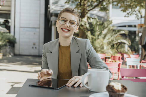 Smiling woman sitting in outdoor cafe - MFF06708