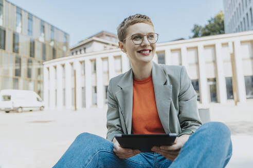 Woman holding digital tablet looking away while sitting on street during sunny day - MFF06753