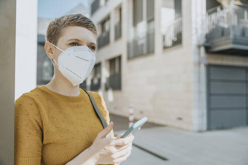 Woman looking away wearing protective face mask using smart during covid-19 - MFF06762