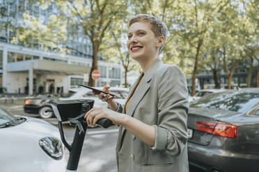 Woman unlocking electric push scooter with smart phone while standing on street in city - MFF06777