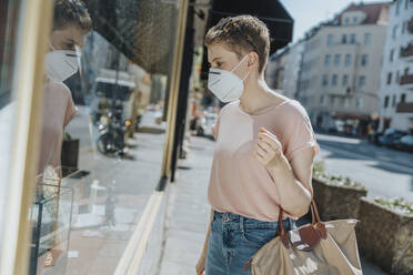 Woman wearing protective face mask doing window shopping while standing on street in city - MFF06783