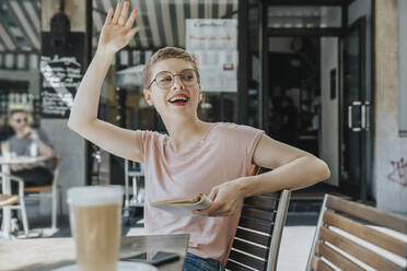 Woman with book waving while sitting in sidewalk cafe on sunny day - MFF06792