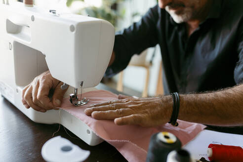Male costume designer sewing fabric while working in studio - VABF03698