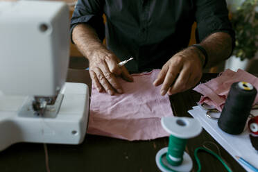 Mature male tailor with fabric working on table in work studio - VABF03704