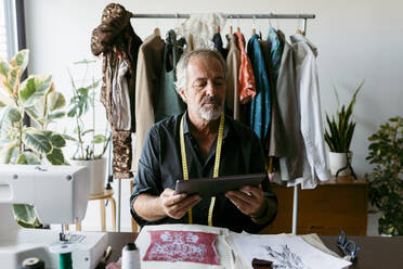 Mature tailor using digital tablet while working at studio - VABF03716