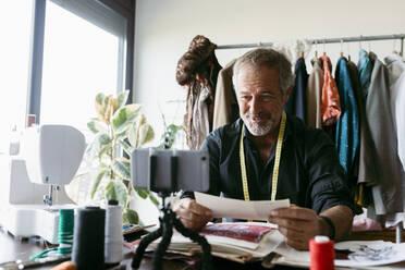 Smiling mature costume designer vlogging at work studio - VABF03725