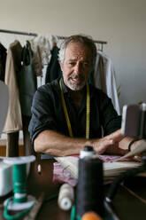 Male costume designer vlogging through smart phone at work studio - VABF03728