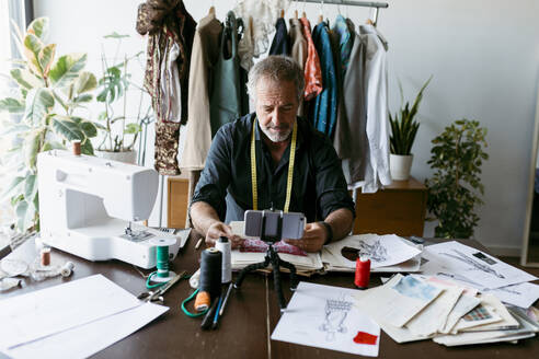 Tailor vlogging using smart phone while sitting at table in studio - VABF03731