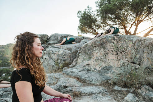 Woman meditating with female friends on rocks against clear sky - MRRF00635