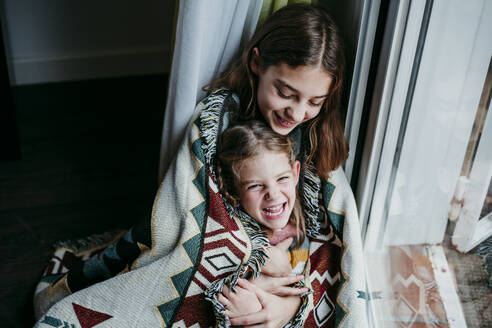 Girl covered in blanket embracing cheerful sister while sitting by window at home - EBBF01113