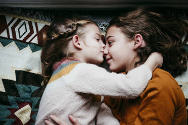 Girl kissing sister while lying on blanket at home - EBBF01119