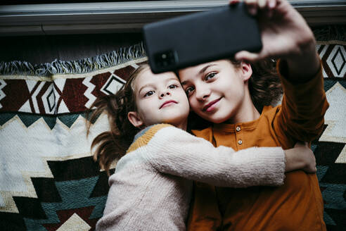 Girl embracing sister while taking selfie through mobile phone at home - EBBF01122