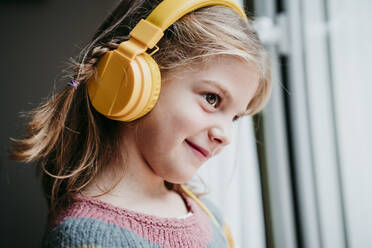 Smiling girl wearing headphones looking through window while standing at home - EBBF01131