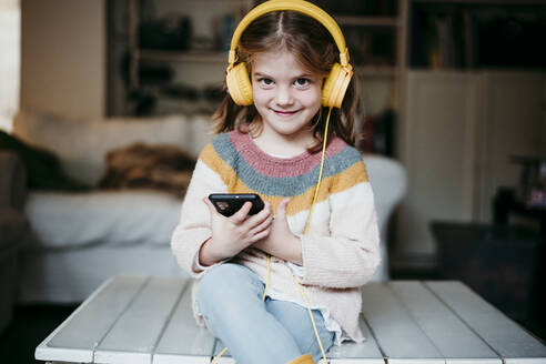 Smiling girl wearing headphones using mobile phone while sitting on table at home - EBBF01134