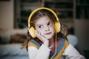 Cute girl wearing headphones with head in hands standing at home - EBBF01137