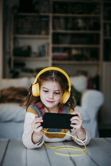 Girl wearing headphones using mobile phone while standing at home - EBBF01140