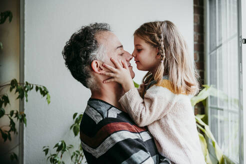 Daughter rubbing nose with father while standing by window at home - EBBF01143