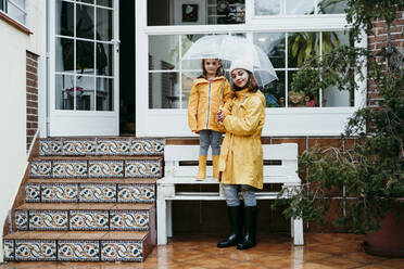Smiling sister holding umbrella by sister standing on bench against home - EBBF01152
