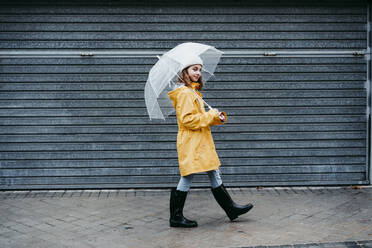 Girl wearing raincoat and jump boot walking on sidewalk outdoors - EBBF01155