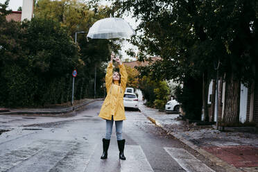 Girl wearing raincoat and jump boot standing on road in city - EBBF01161