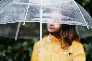 Girl in raincoat holding umbrella while standing outdoors - EBBF01164