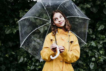 Thoughtful girl smiling while holding umbrella against leaf wall - EBBF01167