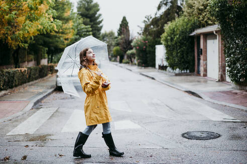 Smiling girl in raincoat holding umbrella while walking on road in city - EBBF01170