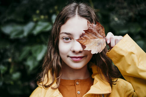 Smiling girl in raincoat hiding eye with dry ivy leaf while standing against leaf wall - EBBF01173