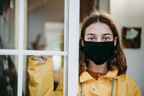 Girl wearing raincoat and face mask standing by door at home - EBBF01176