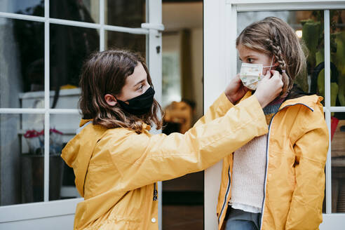 Sister adjusting face mask of sister while sitting against door - EBBF01179