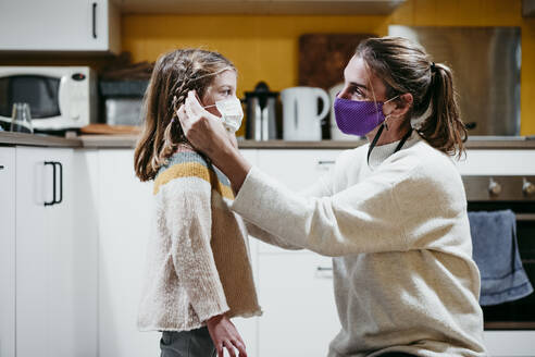 Mother adjusting daughter face mask while sitting at home - EBBF01182
