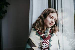 Girl covered in blanket smiling while sitting by window at home - EBBF01191