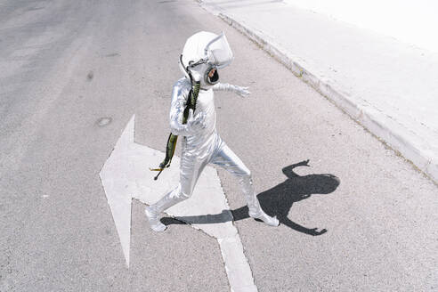 Boy wearing astronaut costume walking on road in city - JCMF01586