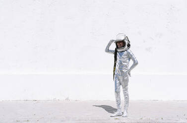 Smiling boy in astronaut costume saluting while standing against wall - JCMF01589