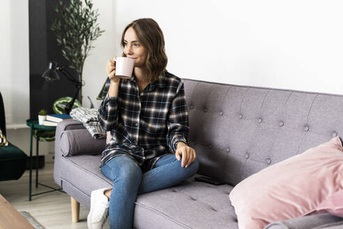 Woman drinking coffee while sitting on sofa at home - GIOF09330
