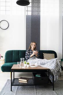 Young woman drinking coffee while relaxing on sofa at home - GIOF09345